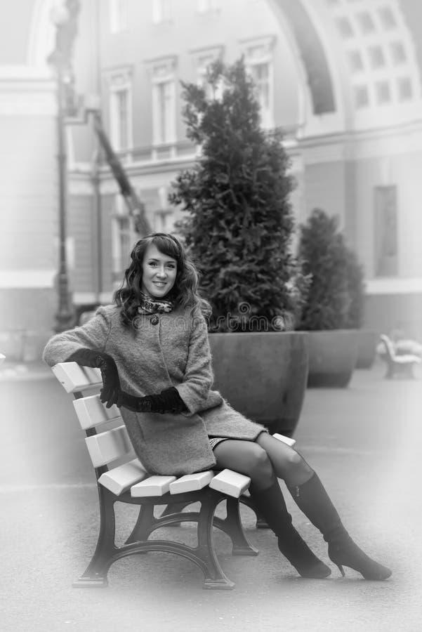 Kvinna i lagsammanträde på en bänk arkivbild