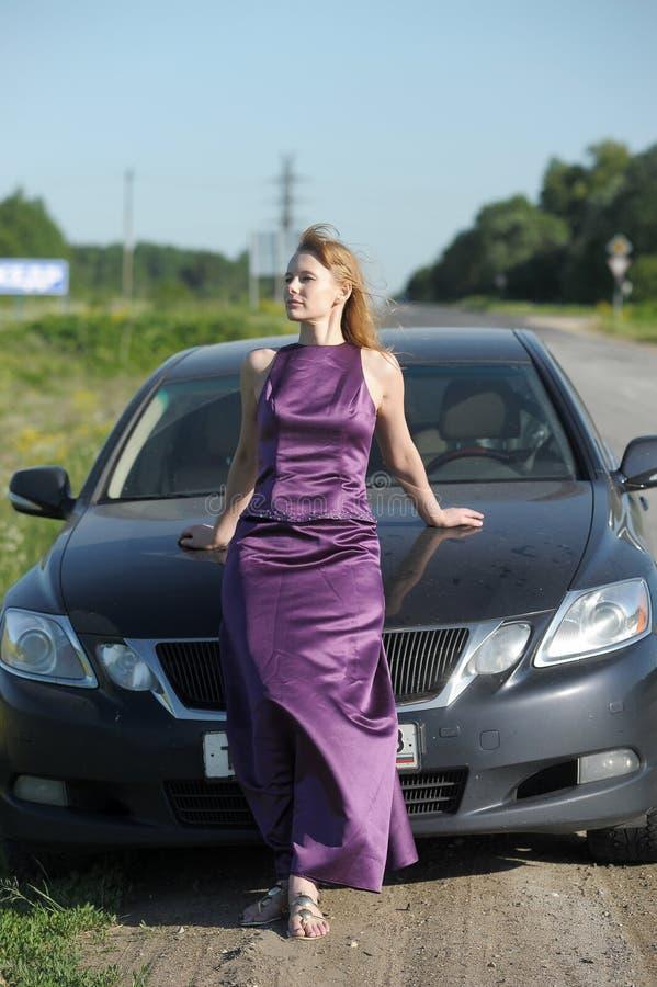 Kvinna i lila klänning för lång afton fotografering för bildbyråer