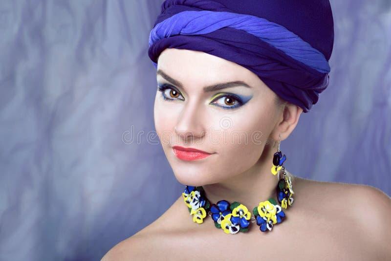 Kvinna i lilor i smycken av pansies fotografering för bildbyråer