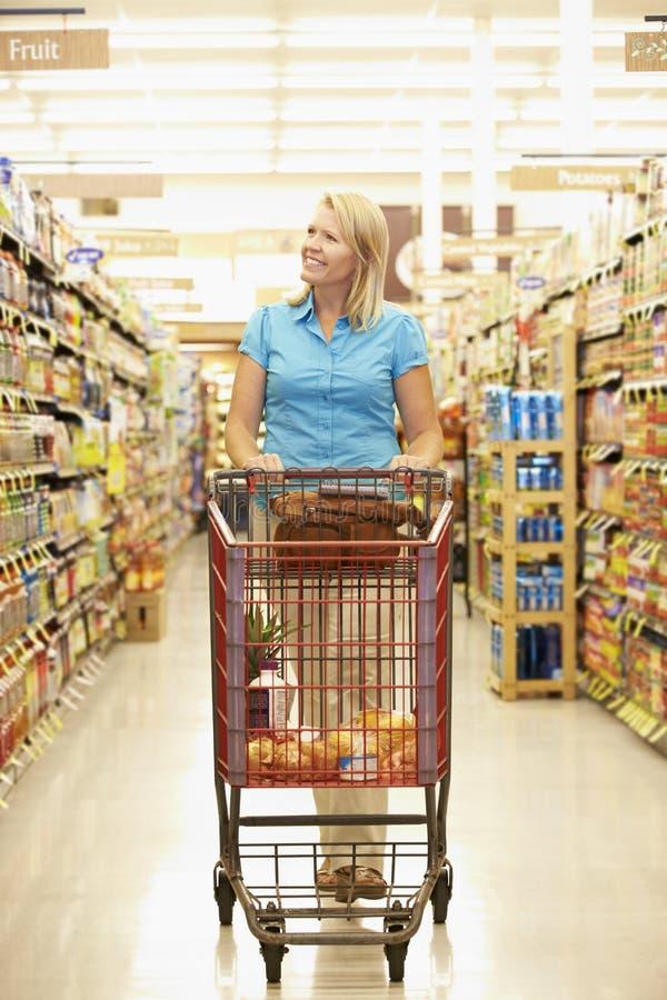 Kvinna i livsmedelsbutikgång av supermarket royaltyfria bilder