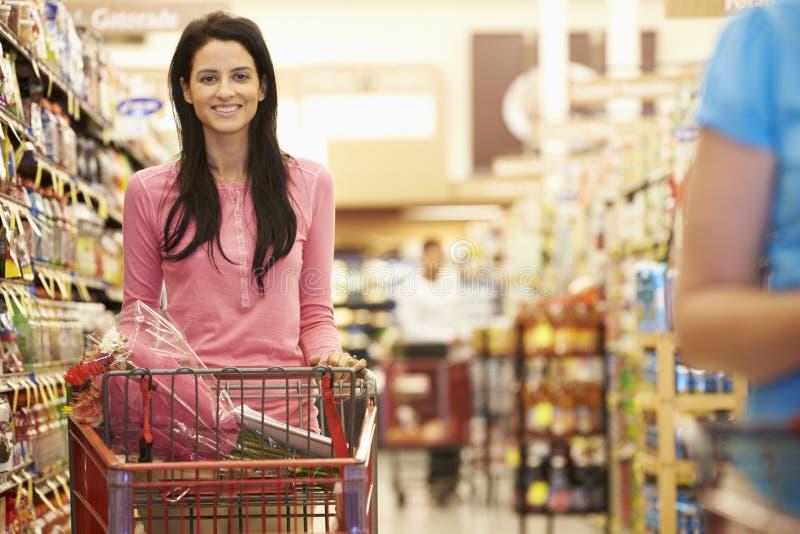 Kvinna i livsmedelsbutikgång av supermarket royaltyfri bild