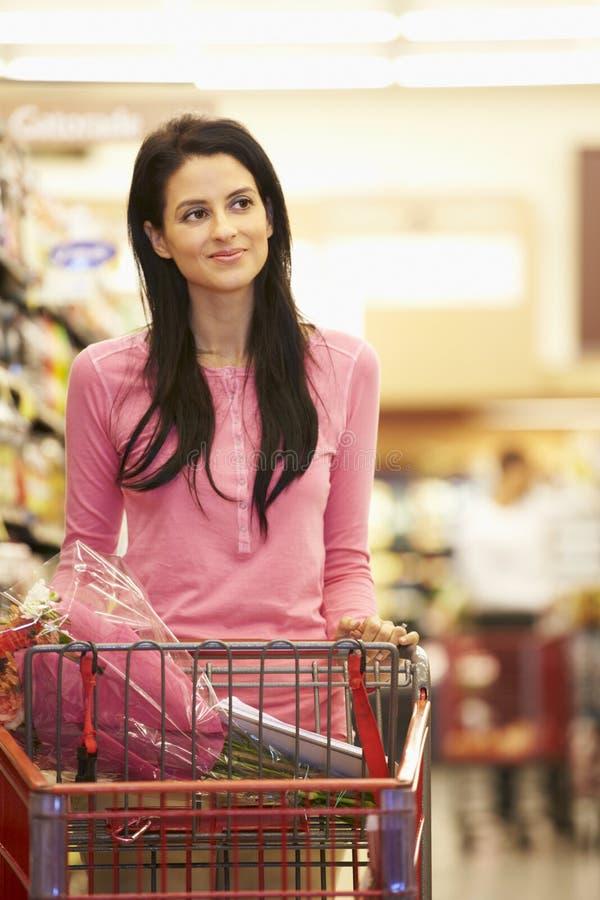 Kvinna i livsmedelsbutikgång av supermarket royaltyfri fotografi