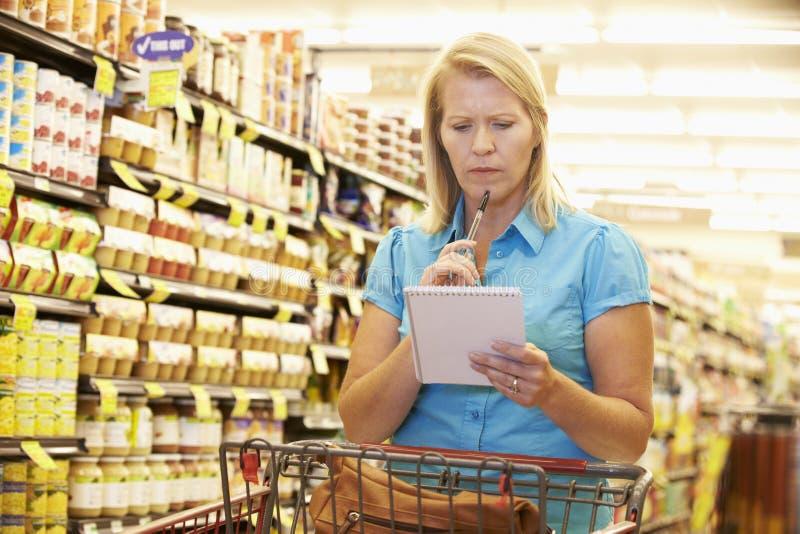 Kvinna i livsmedelsbutikgång av supermarket med listan royaltyfri bild