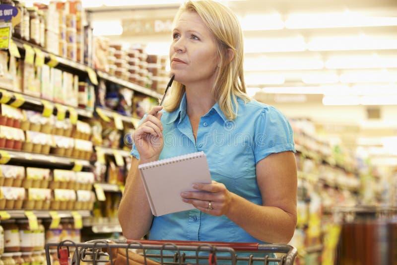 Kvinna i livsmedelsbutikgång av supermarket med listan royaltyfria bilder