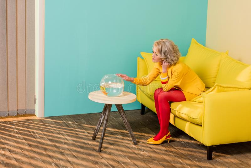 kvinna i ljusa retro kläder som ser akvariefisken, medan vila på soffan på den färgrika lägenheten, docka arkivbilder