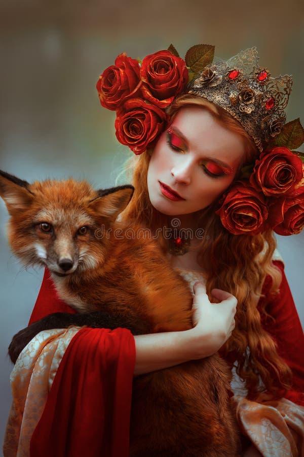 Kvinna i medeltida kläder med en räv arkivfoto