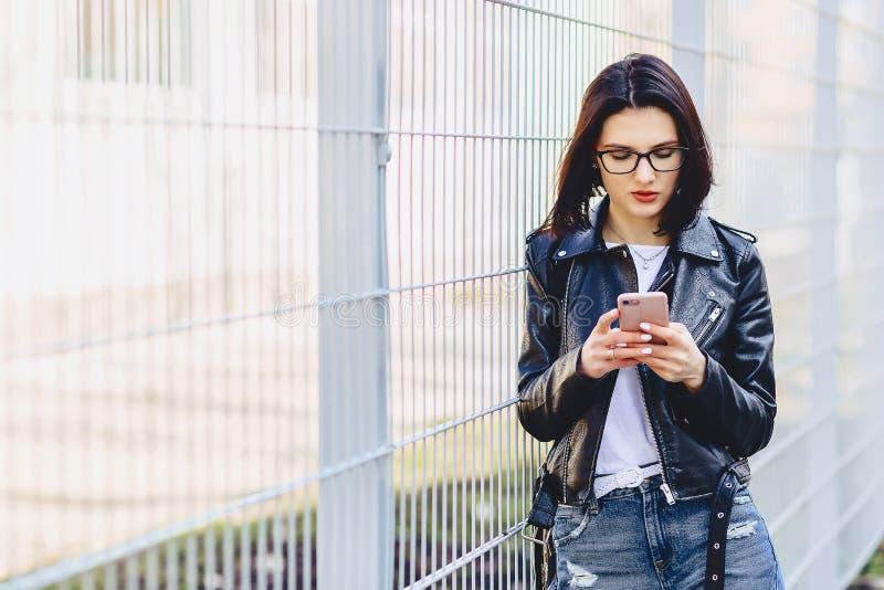 Kvinna i messaging för läderomslag på telefonen på gatan royaltyfria foton