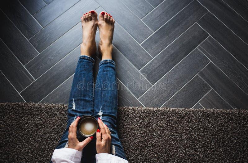 Kvinna i moderiktig jeans som sitter p? det tr?gr?a golvet, driking kaffe B?sta sikt, slut upp royaltyfri fotografi