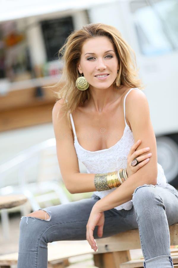 Kvinna i moderiktig kläder som utomhus sitter fotografering för bildbyråer