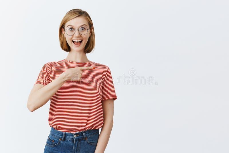 Kvinna i nöjesfältet som det är glat och lyckligt och att rida alla rollercoasters och att peka rätt med pekfingret och att le royaltyfri fotografi