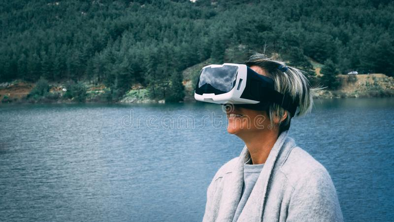 Kvinna i naturen som bär ökad verklighetskyddsglasögon royaltyfri bild