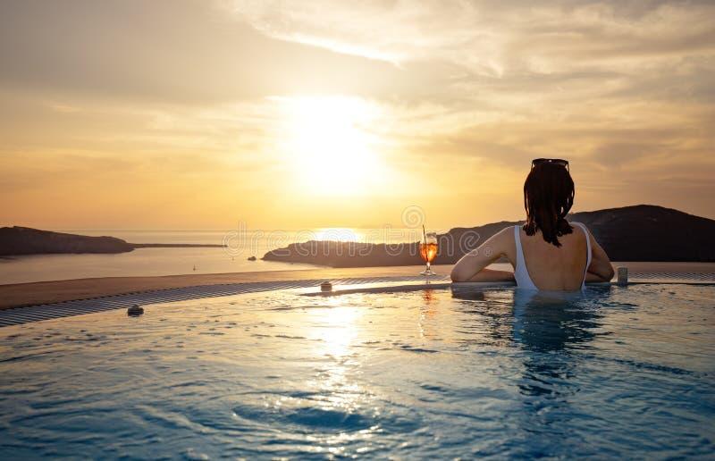 Kvinna i oändlighetssimbassäng på den guld- solnedgången Ferie f?r sommarsemester royaltyfri bild