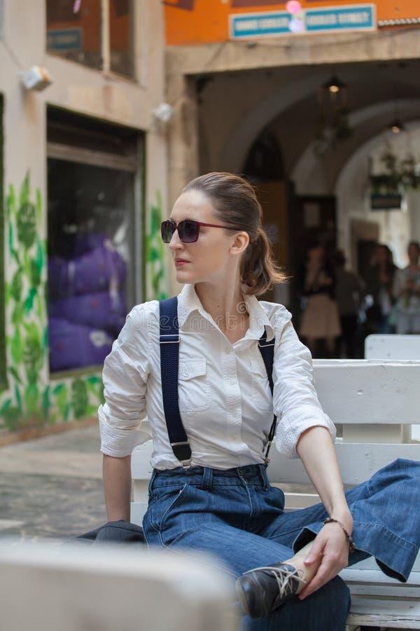 Kvinna i omslag och jeans som g?r p? gatan Gladlynt stilfull kvinna med utomhus- solglas?gon B?rande skuggor f?r kvinna medan loo arkivbilder