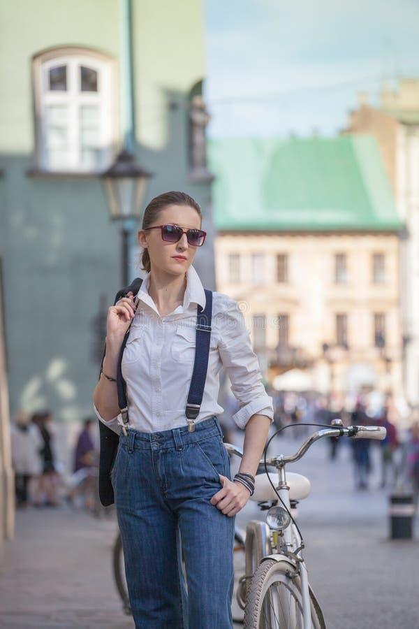 Kvinna i omslag och jeans som g?r p? gatan Gladlynt stilfull kvinna med utomhus- solglas?gon B?rande skuggor f?r kvinna medan loo arkivfoto