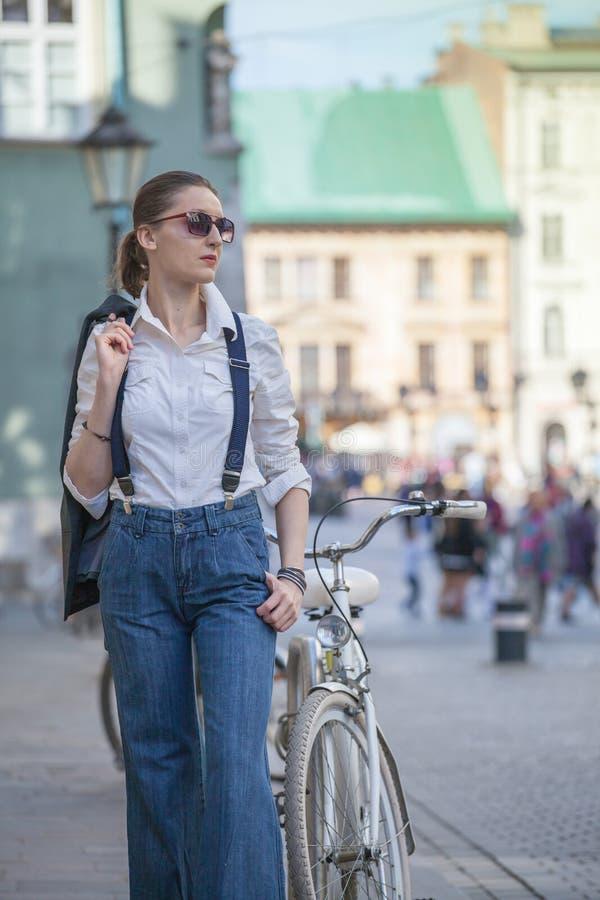 Kvinna i omslag och jeans som g?r p? gatan Gladlynt stilfull kvinna med utomhus- solglas?gon B?rande skuggor f?r kvinna medan loo arkivfoton