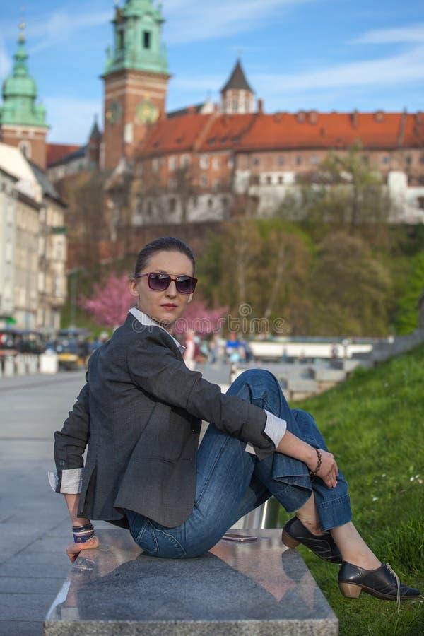 Kvinna i omslag och jeans som g?r p? gatan Gladlynt stilfull kvinna med utomhus- solglas?gon B?rande skuggor f?r kvinna medan loo royaltyfria bilder
