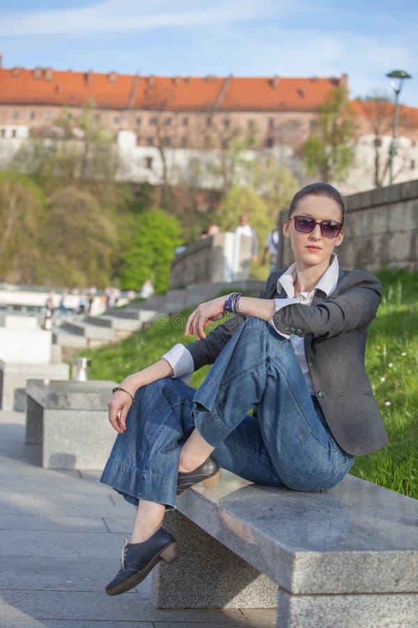 Kvinna i omslag och jeans som g?r p? gatan Gladlynt stilfull kvinna med utomhus- solglas?gon B?rande skuggor f?r kvinna medan loo royaltyfri fotografi
