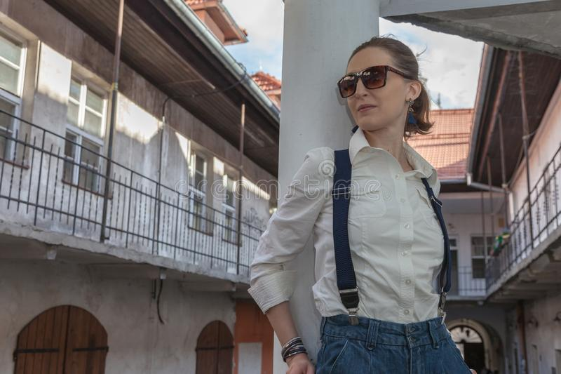Kvinna i omslag och jeans som g?r p? gatan Gladlynt stilfull kvinna med utomhus- solglas?gon B?rande skuggor f?r kvinna medan loo royaltyfri foto