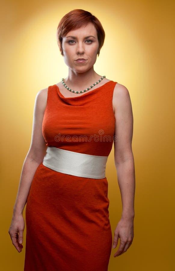 Kvinna i orange retro klänning arkivbilder