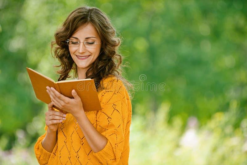 Kvinna i orange tröjaavläsning arkivfoton