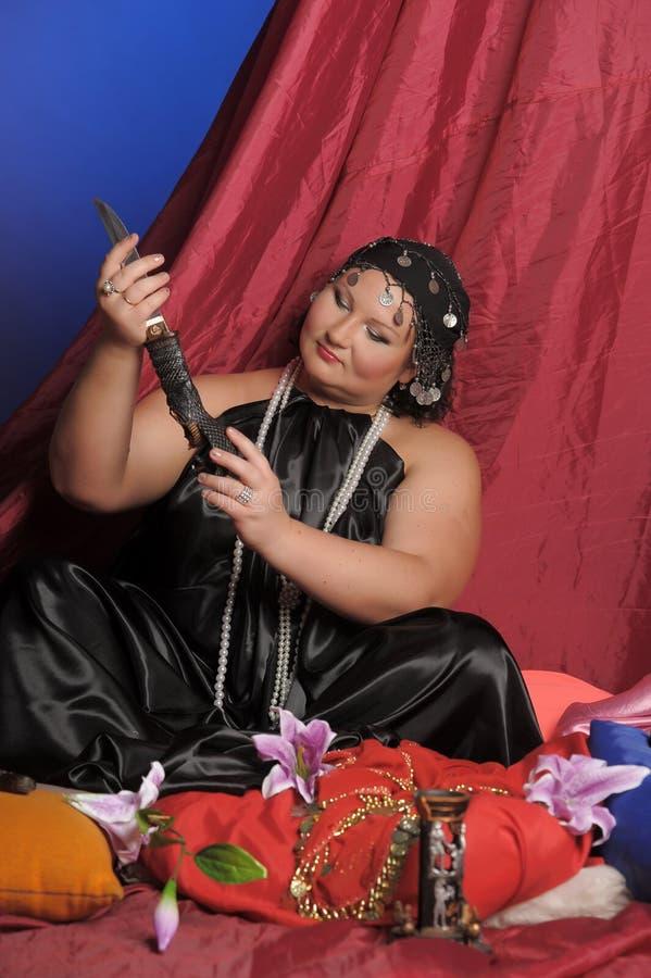 Kvinna i orientalisk kl?der med en kniv royaltyfri bild