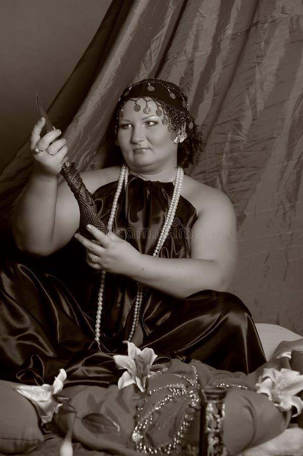 Kvinna i orientalisk kl?der med en kniv arkivfoto