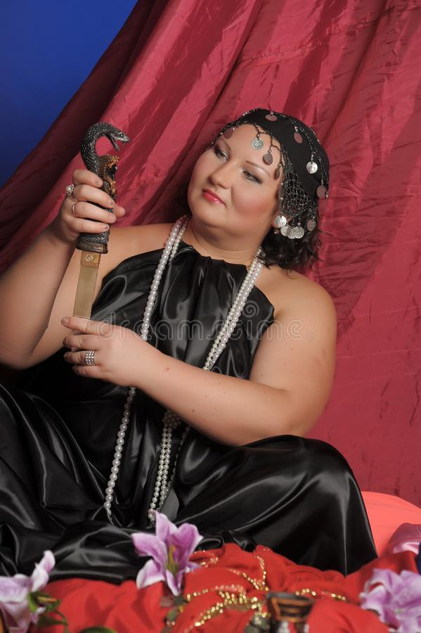 Kvinna i orientalisk kl?der med en kniv arkivbild