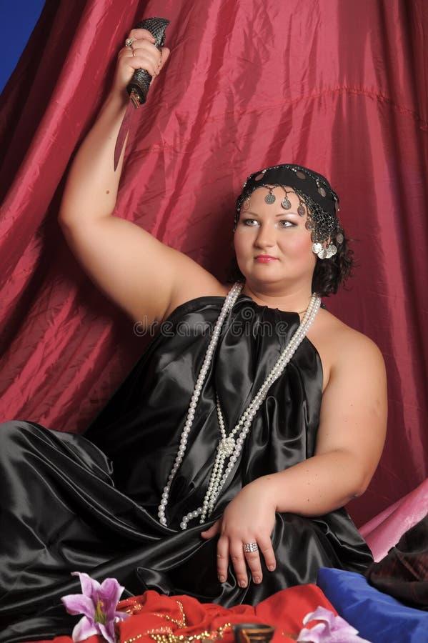 Kvinna i orientalisk kl?der med en kniv arkivfoton