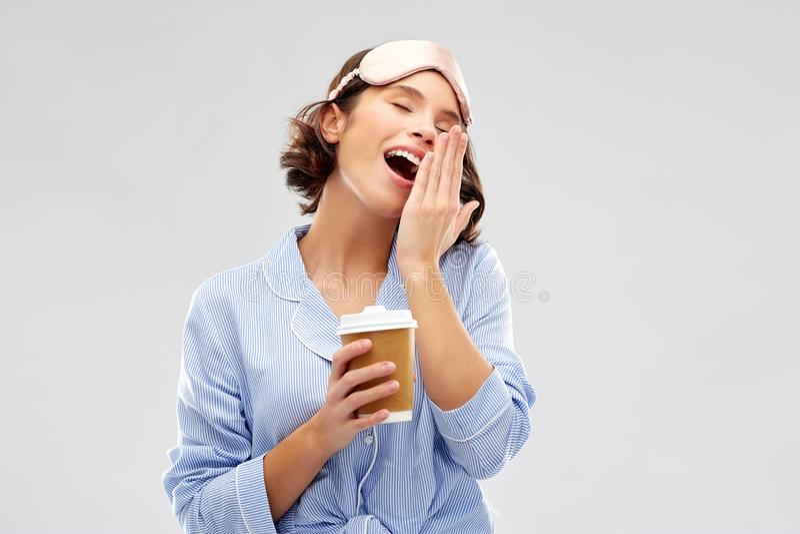 Kvinna i pajama- och ögonmaskering med att gäspa för kaffe royaltyfri fotografi