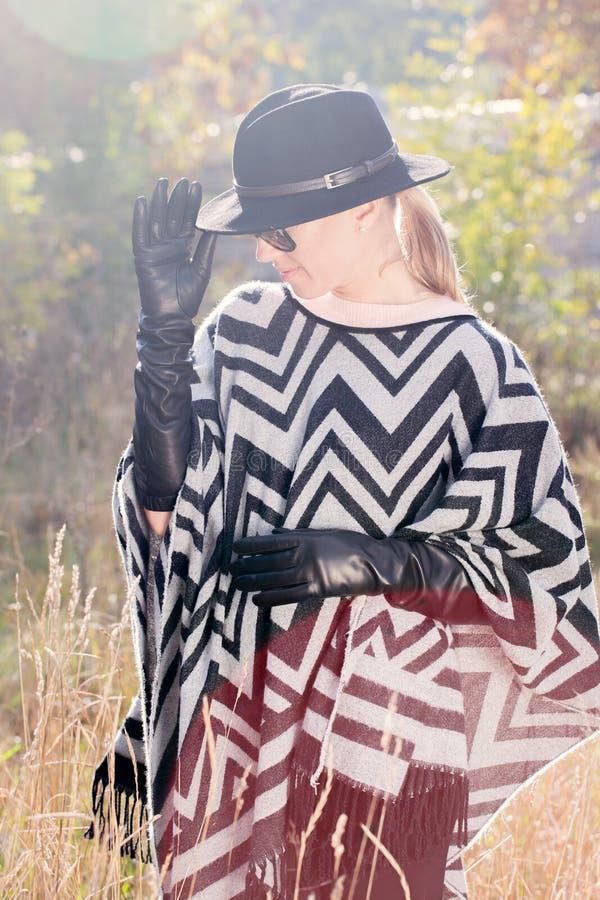 Kvinna i poncho och långa handskar arkivbilder