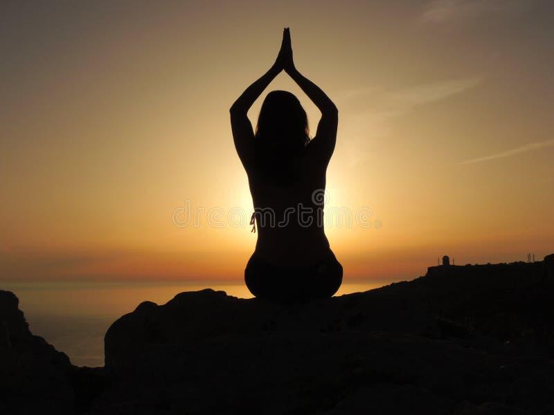 Kvinna i position av tacksamhet på solnedgången royaltyfria bilder