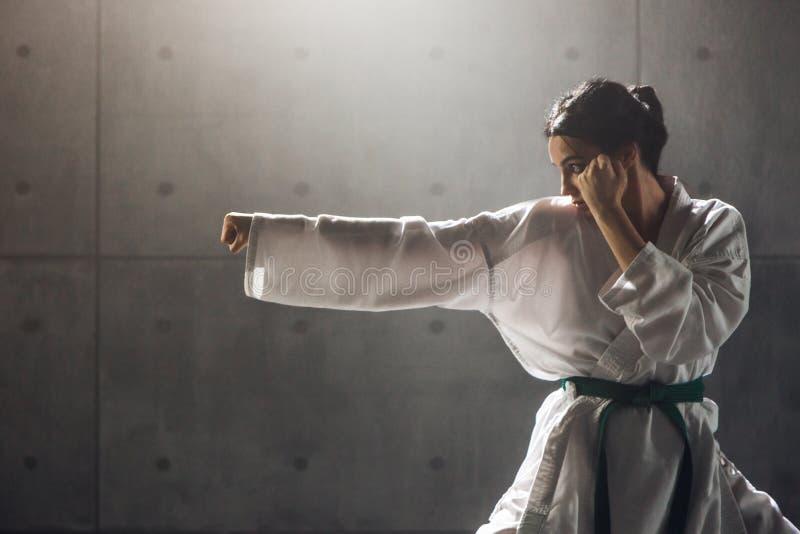 Kvinna i praktiserande karate för kimono arkivbild
