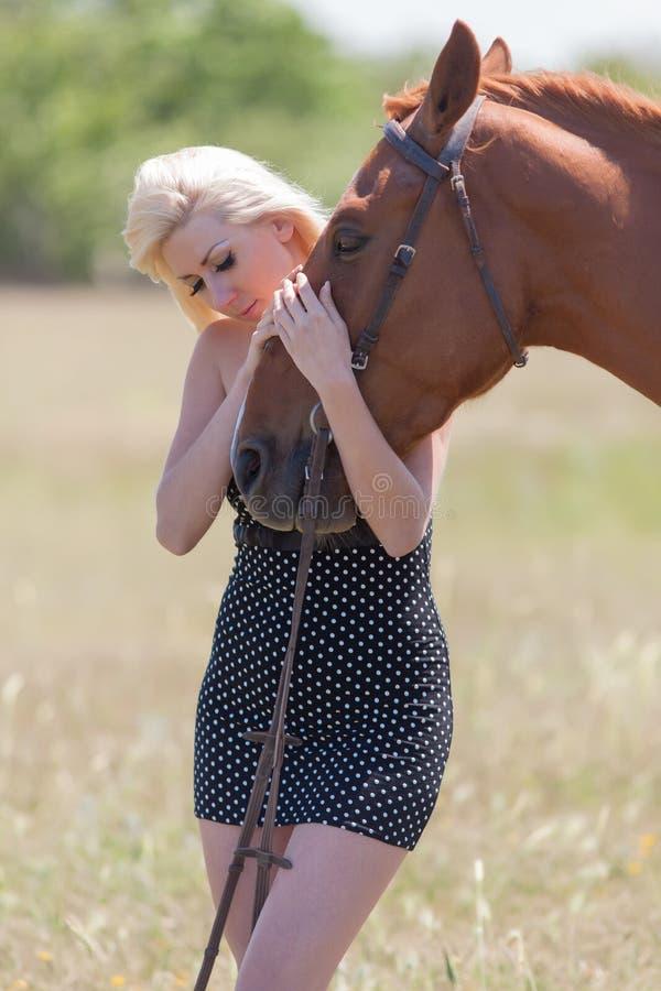Kvinna i prickklänning med den bruna hästen royaltyfria bilder