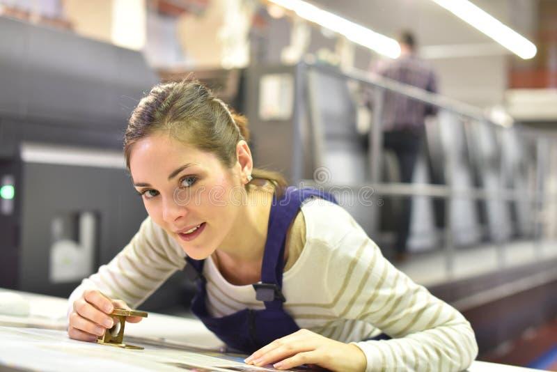 Kvinna i printinghus som kontrollerar produktionkvalitet royaltyfri bild
