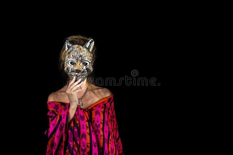 Kvinna i purpurfärgad klänning och blåa ögon som rymmer en katt- maskeringscoveri arkivbild