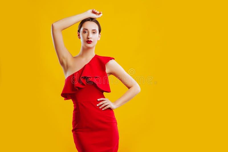 Kvinna i röd klänning över gul bakgrund royaltyfria bilder