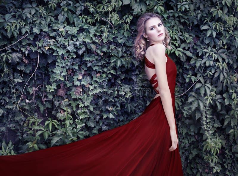 Kvinna i röd klänning, i den hemliga trädgården royaltyfria foton