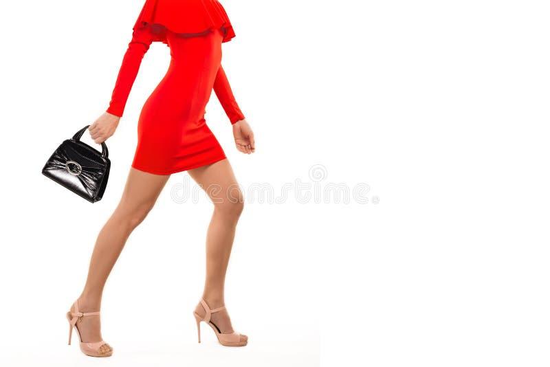 Kvinna i röd klänning i höga häl med handväskan arkivfoton