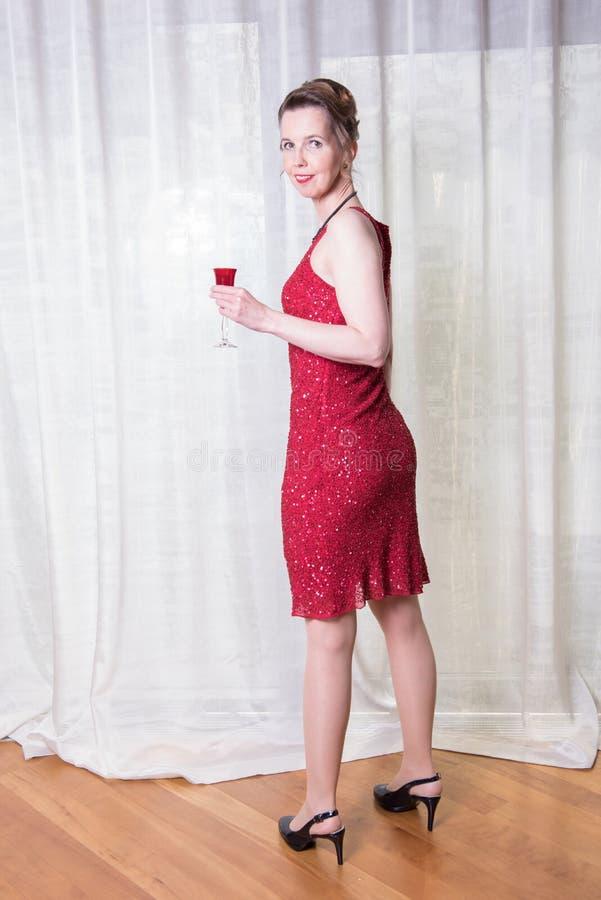 Kvinna i röd klänning med exponeringsglas i hennes hand royaltyfria foton