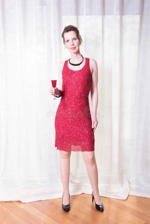 Kvinna i röd klänning med exponeringsglas i hennes hand arkivfoton