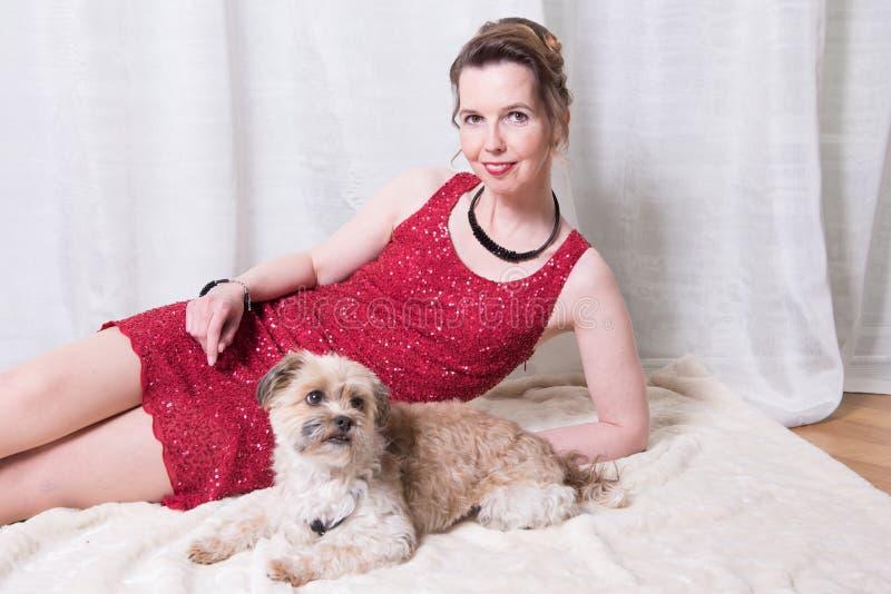 Kvinna i röd klänning med hunden på filten royaltyfri fotografi
