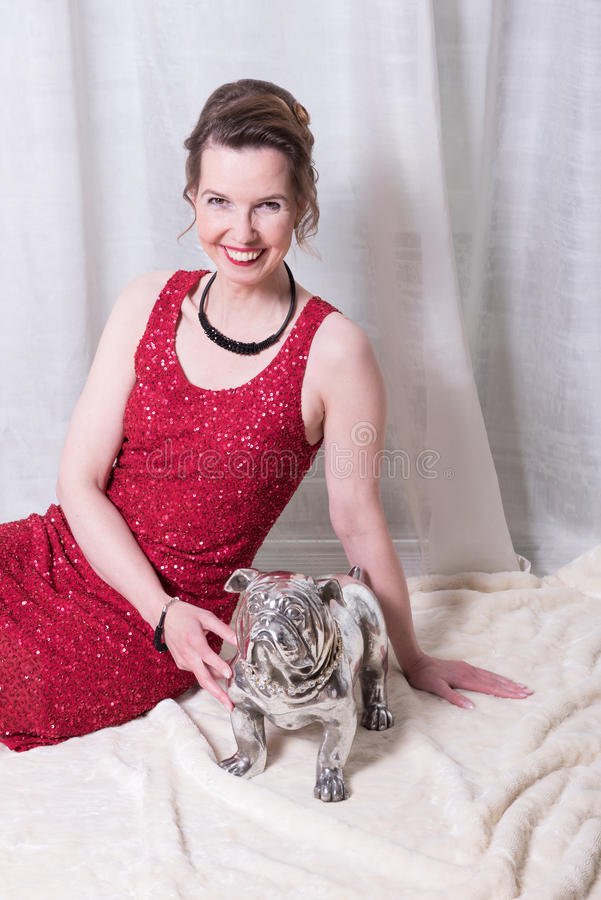 Kvinna i röd klänning med hunden på filten fotografering för bildbyråer