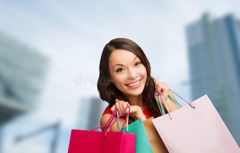 Kvinna i röd klänning med shoppingpåsar arkivbilder