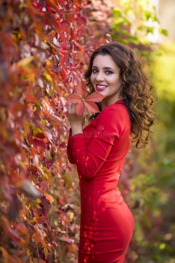 Kvinna i röd klänning på en solig höstdag arkivfoto