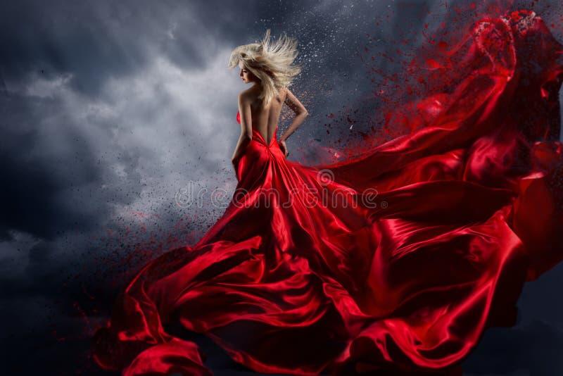 Kvinna i röd klänningdans över stormhimmel, kappa som fladdrar tyg royaltyfri bild