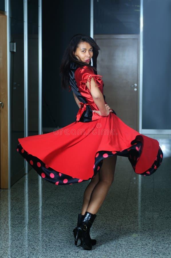 Kvinna i röd klänningdans fotografering för bildbyråer