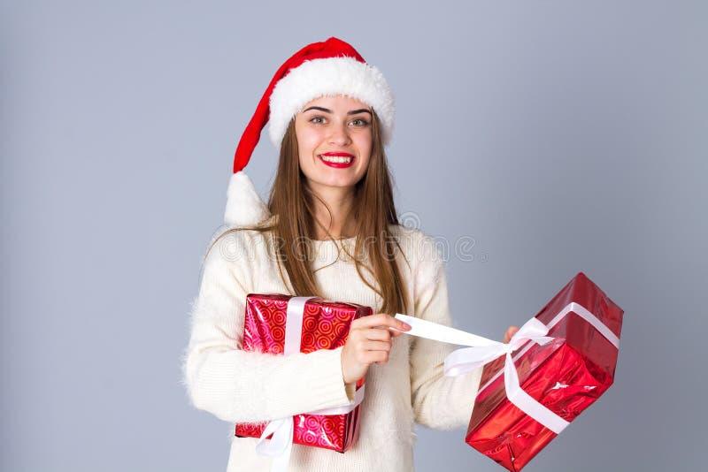 Kvinna i röda gåvor för julhattinnehav royaltyfri bild
