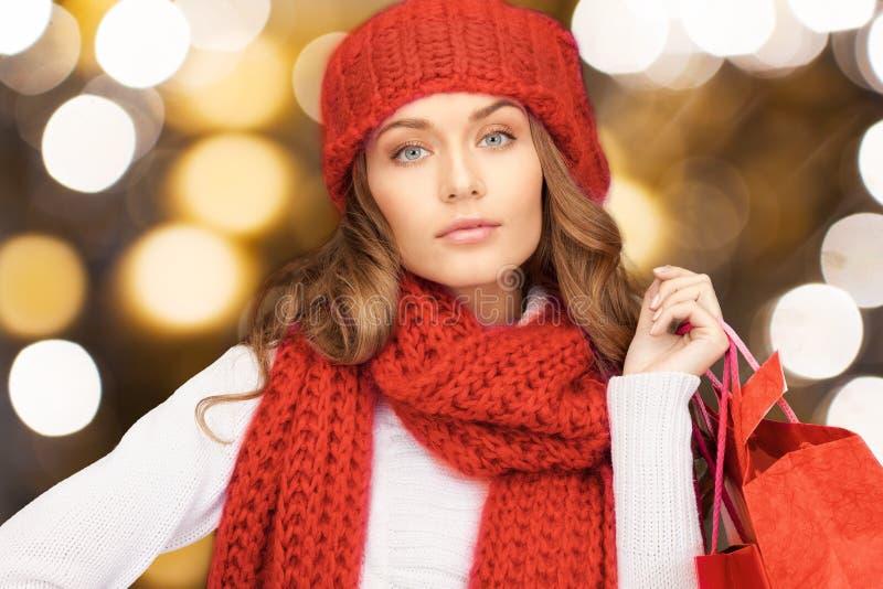 Kvinna i röda hållande shoppingpåsar för hatt och för halsduk royaltyfri foto