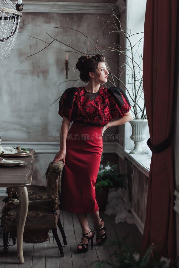 Kvinna i röda klänningblickar på fönstret i grått vindrum med tappningfåtöljen och trätabellen royaltyfri fotografi