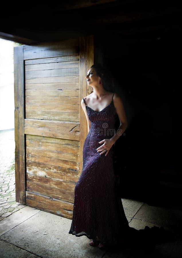 Kvinna i rött anseende för aftonklänning i dörröppning royaltyfri bild